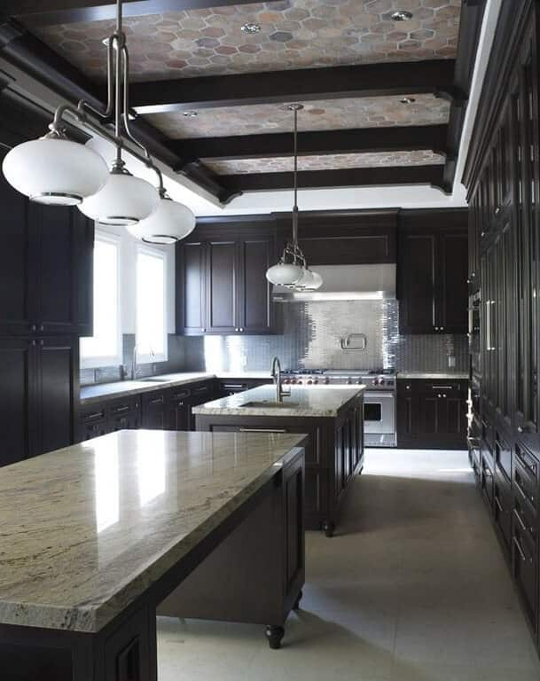 This gorgeous kitchen has a ceiling accented with outdoor hexagonal tiles that pair well with the dark exposed wooden beams. This matches with the dark tone of the cabinetry of the two kitchen islands and the L-shaped peninsula.