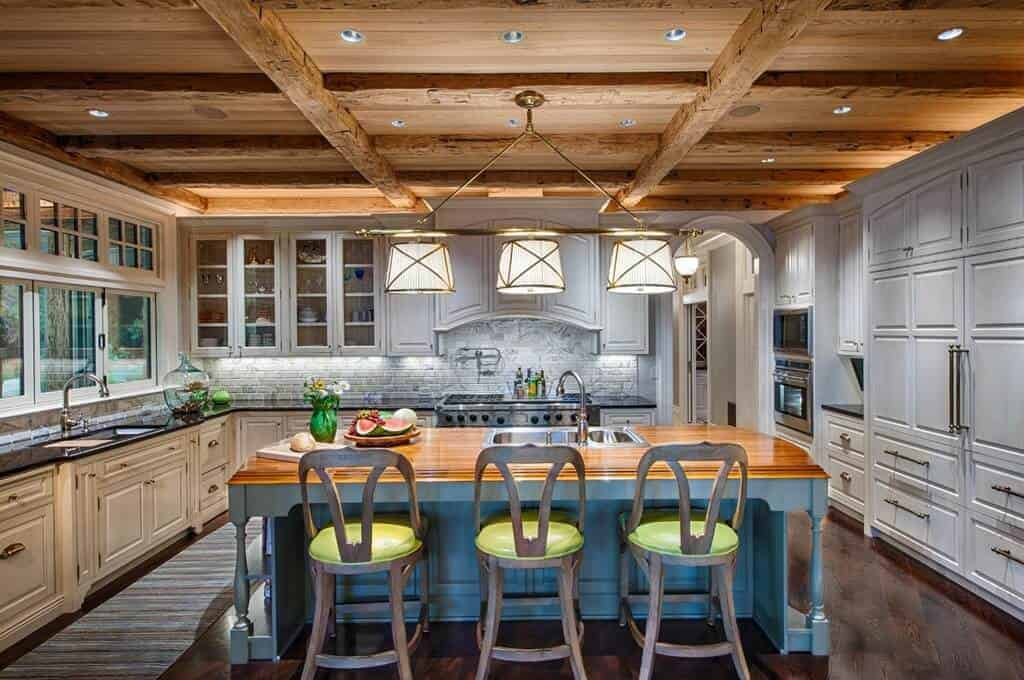 The golden row of pendant lights stand out against the textured wooden ceiling and its rustic exposed wooden beams. This pairs well with the charming wooden light blue kitchen island that has a butcher block countertop and contrasts the dark hardwood flooring.
