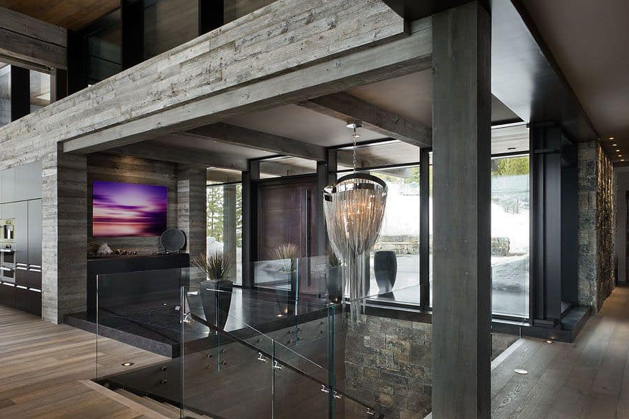 The low ceiling of this foyer and its exposed wooden beams extend to the ceiling of the staircase beside it. This has glass sides and a large decorative chandelier hanging from one of the exposed beams that match the dark flooring marble of the foyer.