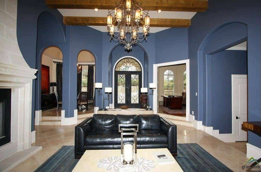The main entrance is clearly seen from the vantage point of the living room that has a black leather sofa by the large fireplace. This is matched with a wrought iron main door making its stand out against the blue walls as well as the wooden exposed beams of the ceiling.