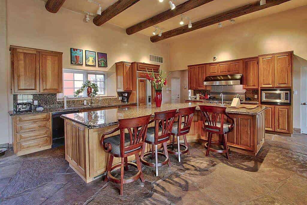 This spacious kitchen has enough room for a large L-shaped kitchen island to match the two kitchen peninsulas with the same wooden cabinetry and dark marble countertop paired with four wooden stools with a red hue that goes well with the wooden log beams of the beige ceiling.