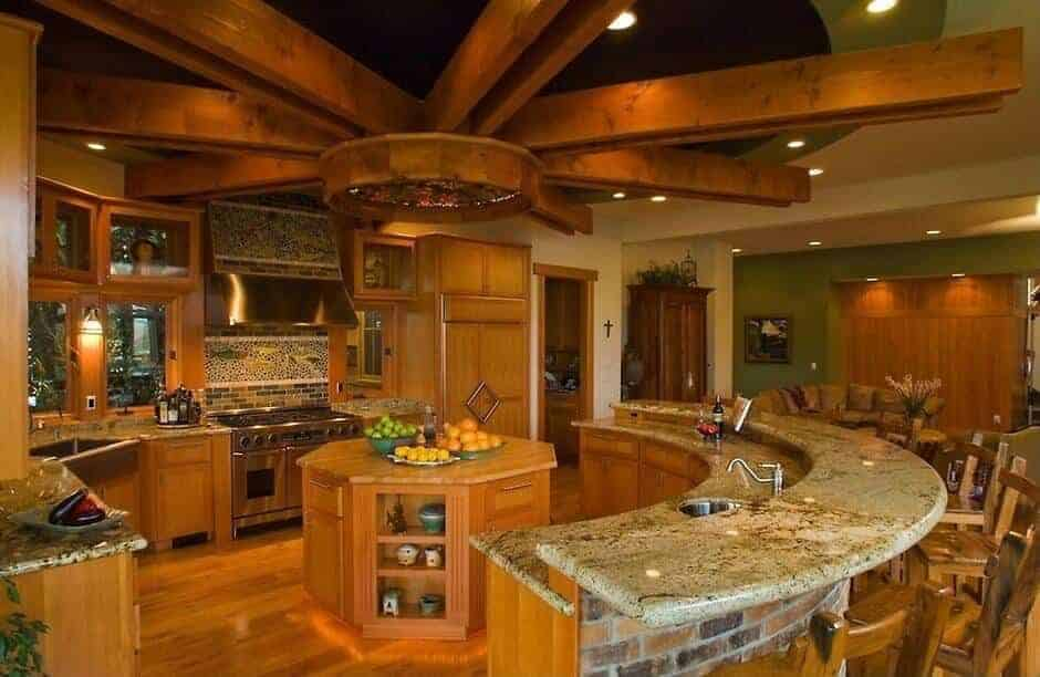 The small octagonal wooden kitchen island in the middle is surrounded by an L-shaped peninsula and a large curved kitchen island that also serves as a breakfast bar. This setup is complemented by a wooden ceiling that has exposed wooden beams designed in a sun-like pattern.