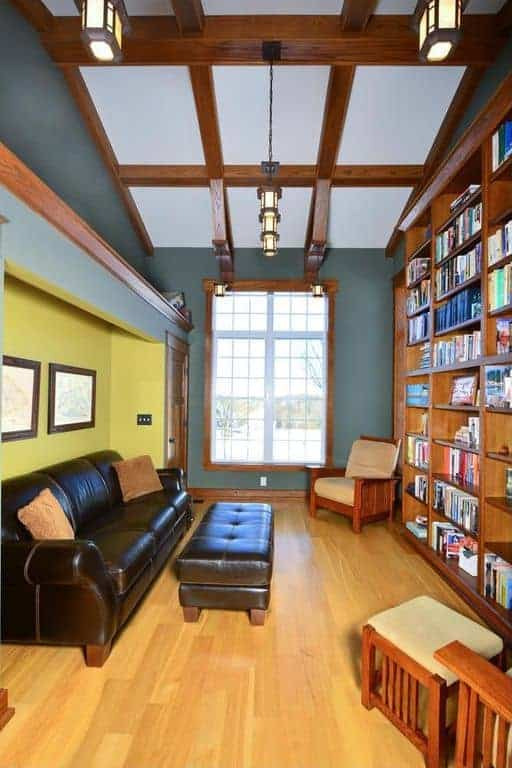 This is a comfortable library that has a little reading nook in an alcove with a large leather sofa that stands out against the light hardwood flooring. This is contrasted by the dark wooden book shelf that goes up to the white ceiling and its matching dark wooden beams.