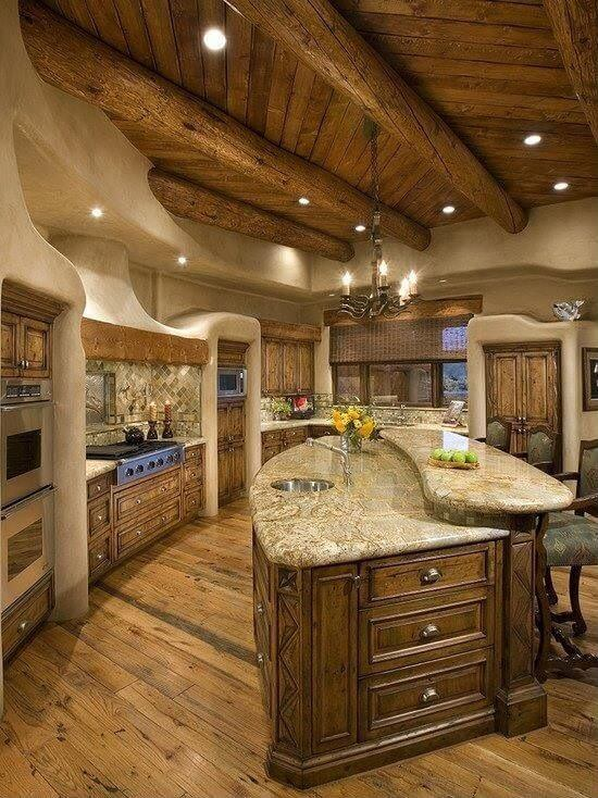 The wooden ceiling and its exposed log beams are a great pairing for the earthy beige walls that extend fluidly to the wooden structures of the kitchen peninsula as if it was clay shaped by hand. This is matched by sand-colored countertops and the hardwood flooring.