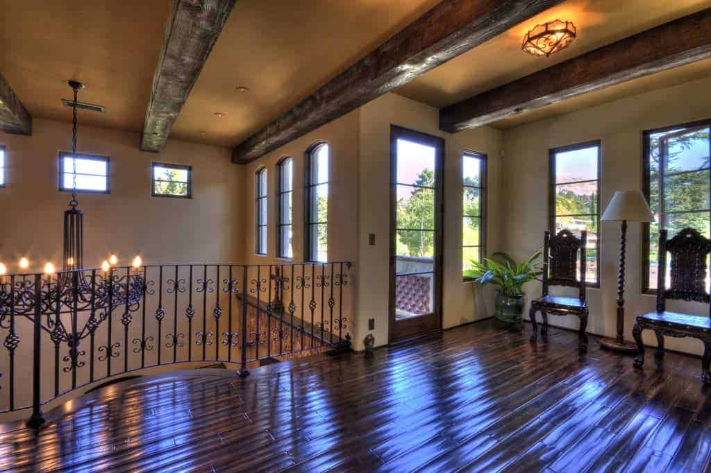 This is a second floor landing with a textured dark wooden flooring that looks like its dark water. This pairs well with the wrought iron railings, thick dark wooden beams of the ceiling as well as the two wooden chairs placed by the windows.