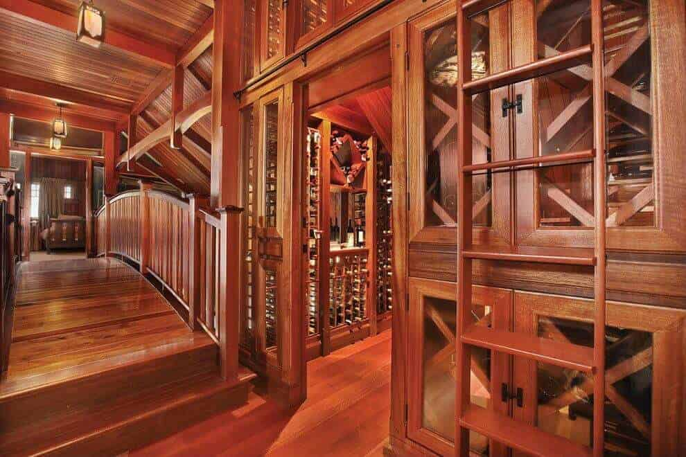This is a beautiful redwood hallway within the home with a small curved bridge in the middle topped with a ceiling of the same redwood hue as well as its exposed beams that hangs lanterns that cast off warm yellow lights as it leads you to the wine cellar.
