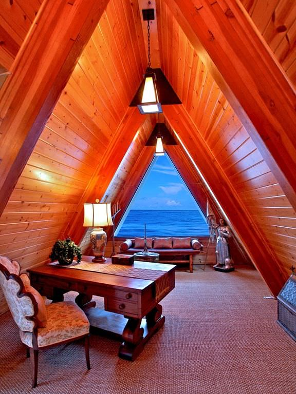 This small and cozy home office has a low cathedral wooden ceiling with exposed wooden beams that matches with the wooden desk and the cushioned bench by the triangular window that showcases a beautiful water scenery beyond the house.