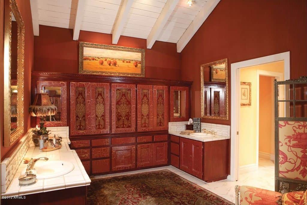 The dark red cabinetry of this primary bathroom blends with the two vanities with shaker cabinets and drawers. This tone also extends to the walls contrasted by the bright white ceiling and its exposed wooden beams matching the countertops and the flooring mostly covered by a red patterned area rug.