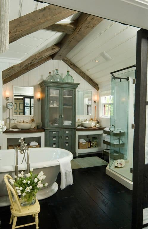 This small and charming bathroom has an irregular arch to its wooden shiplap ceiling with thick exposed beams that contrast the white ceiling. This extends to the white shiplap walls that serve as a good background for the vanity and bathtub that stands out against the pitch black hardwood flooring.