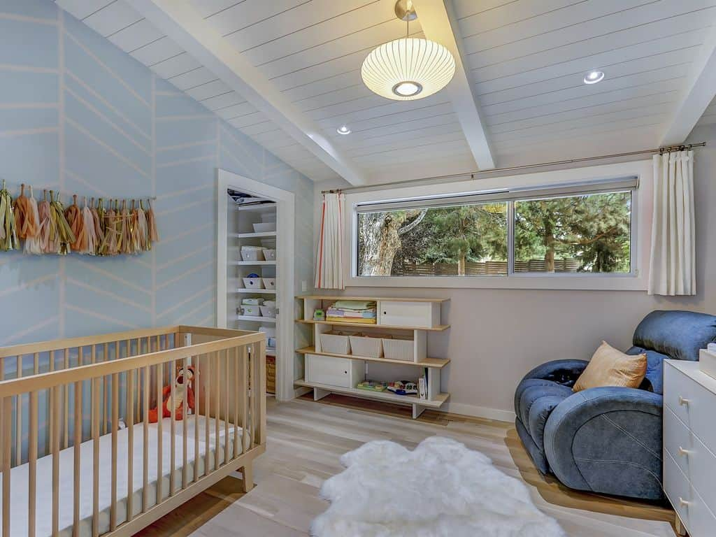 This is a beautiful nursery with a cheerful light blue wall to complement the wooden crib placed against it as well as the white shiplap plank ceiling with exposed wooden beams of the same hue. This hangs a round decorative pendant light over the white area rug of the light hardwood flooring.