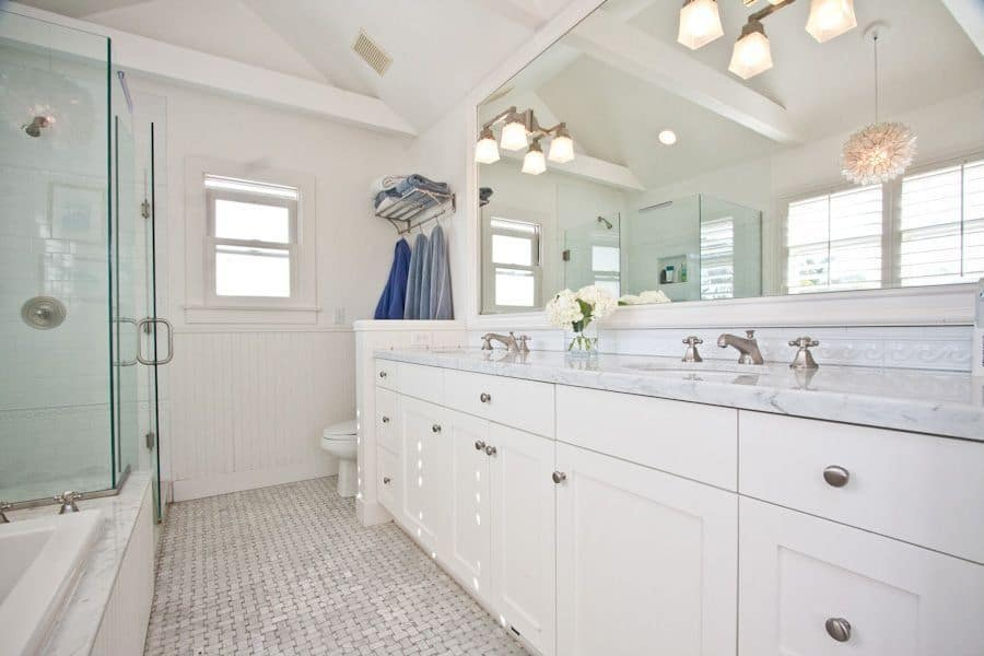 The bright and white walls of this bathroom is a perfect match for the white ceiling and its exposed beams above the shower that is enclosed within glass walls beside the bathtub that is placed across from the white cabinetry of the two-sink vanity topped with a large mirror.