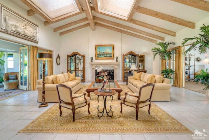 This large and cavernous living room is illuminated by the two expansive skylights on the cathedral ceiling supported by the thick exposed wooden beams. This brightens the beige velvet sofas, beige cushioned wooden armchairs and the matching large beige patterned area rug.