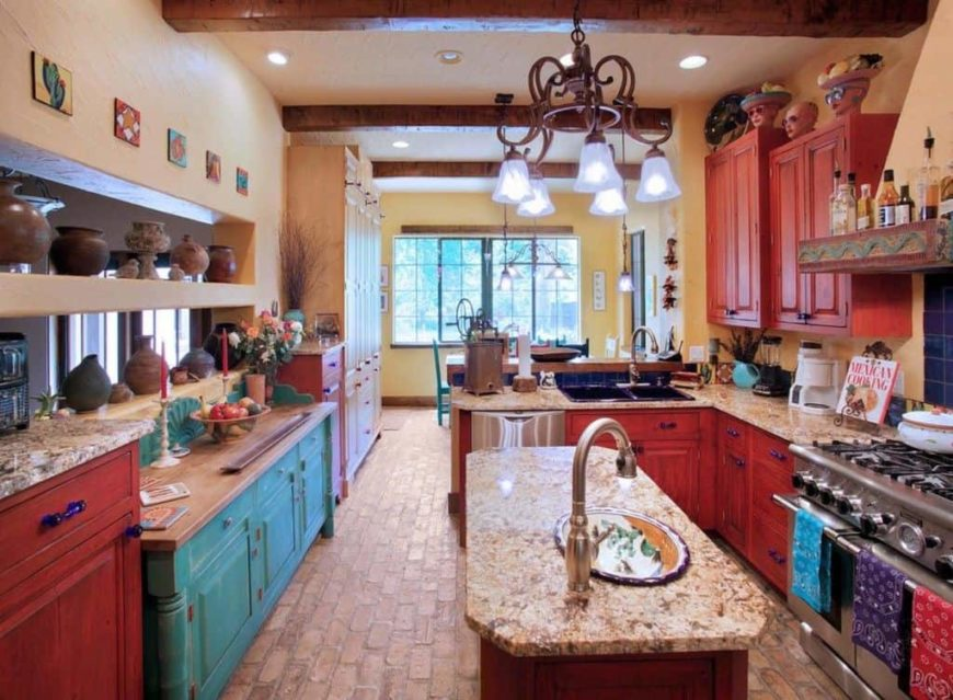 This kitchen has a shabby chic element to its wooden cabinetry of the kitchen island and peninsula that has redwood and blue tones. These goes well with the earthy brick flooring, beige walls and ceiling that has exposed beams supporting a thick wrought iron chandelier.