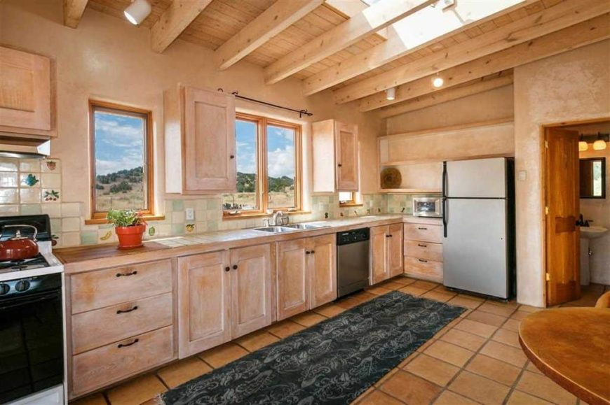 This bright kitchen has a consistent light wooden tone to its exposed wooden beams of the ceiling, cabinets and drawers of the L-shaped peninsula. These are brightened by the windows and the skylight contrasted by the terracotta flooring tiles.