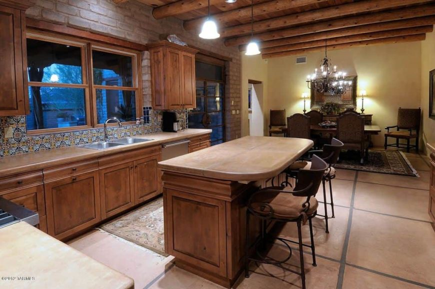 On the far end of this great room is the dining area that has a brown dining set that stands out against its beige walls and patterned area rug. Next to it is the kitchen that has the same hue on the wooden peninsula and island as it wooden ceiling and its exposed beams.