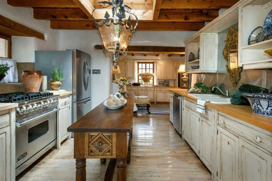 The large decorative lantern pendant light hanging over the small wooden table dominates the wooden ceiling and its exposed beams. This dark wooden table serves as a small kitchen island that is surrounded by the white distressed cabinetry of the peninsulas.
