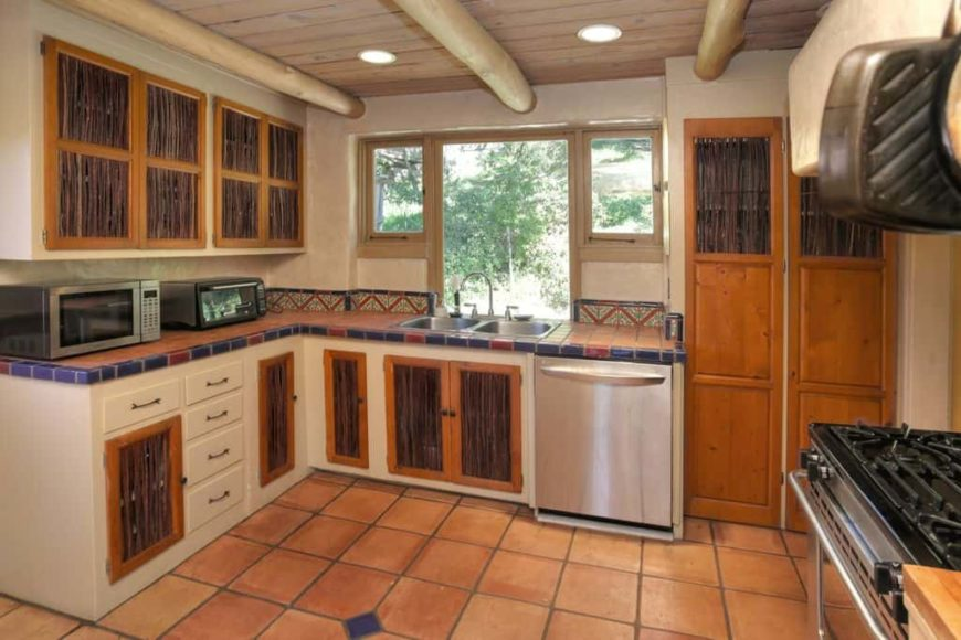 The cabinetry of this small and charming kitchen is adorned with dark brown wicker-like strips that contrast the wooden tone of the cabinets with an orange tinge that complements the terracotta flooring tiles and the colorful backsplash tiles of the L-shaped peninsula.