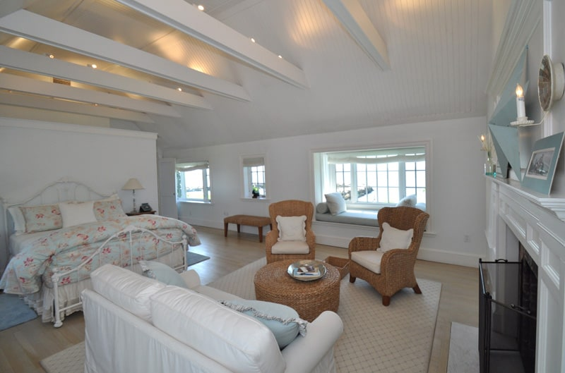 This is a bright and comfortable primary bedroom with a stark white cathedral ceiling with exposed beams paired with white walls that blend with the white wrought iron frame of the bed. There is a sitting area by it foot with woven wicker furniture next to the fireplace.