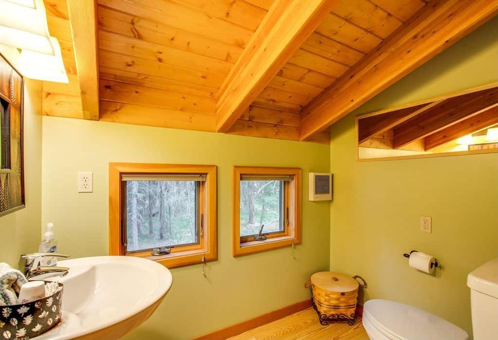 This is a small and charming Cottage-style bathroom with green walls to pair the wooden exposed beams of the shed ceiling. This wooden hue is also seen on the window frames and the hardwood flooring that makes the white porcelain toilet and floating sink stand out.