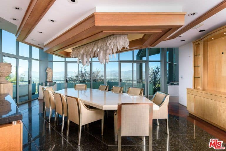 Modern dining room featuring black tiles flooring and a stunning custom ceiling. The room offers a custom white dining table with classy chairs surrounded by glass doors and windows.