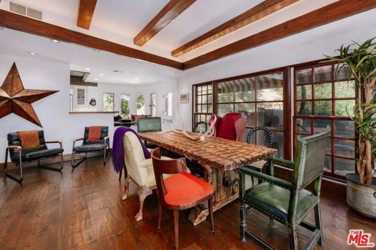 A spacious dining room featuring a ceiling with beams, along with white walls and hardwood floors. The room offers a gorgeous dining table with stylish chairs.
