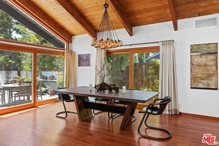 This dining area boasts a stunning wooden ceiling and hardwood floors, along with glass windows and doors. The area offers a stylish dining table set with modern chairs.