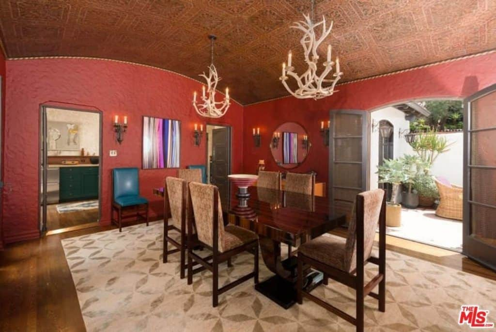 Dining room with a stunning brown decorated ceiling and red walls, along with hardwood flooring topped by an area rug where the gorgeous dining table and chairs are set, lighted by charming ceiling lights.