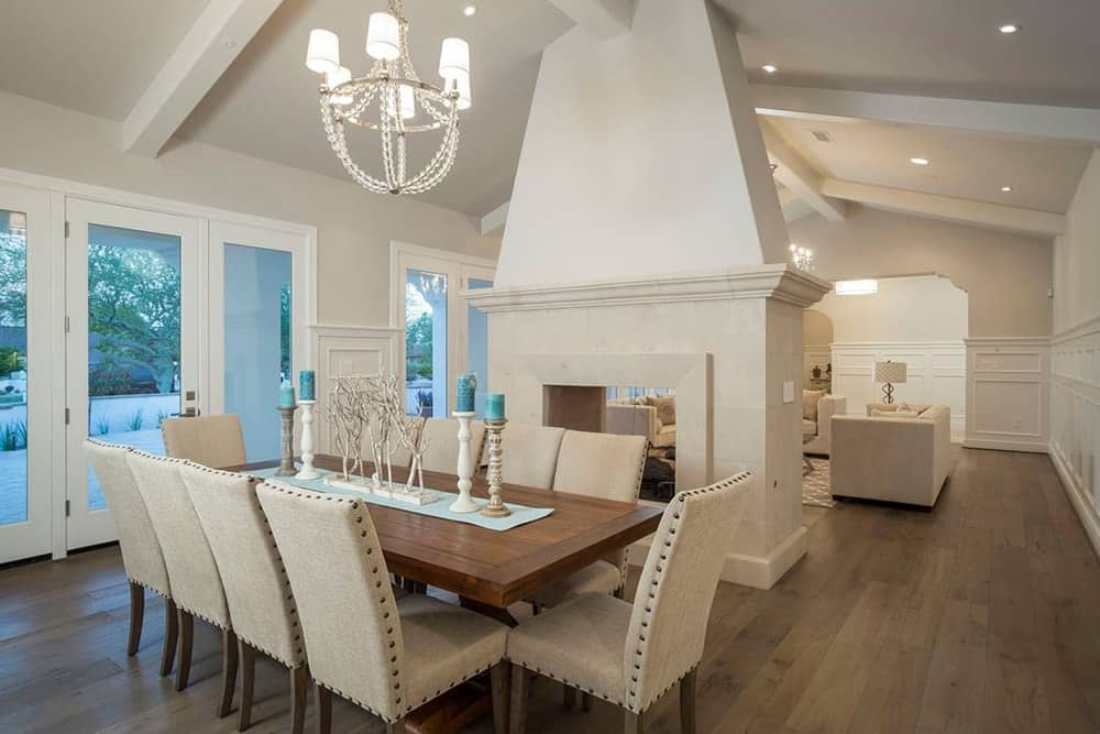 A dining room with a tall white ceiling and hardwood flooring. The area offers a wooden dining table with white classy chairs lighted by a charming chandelier.