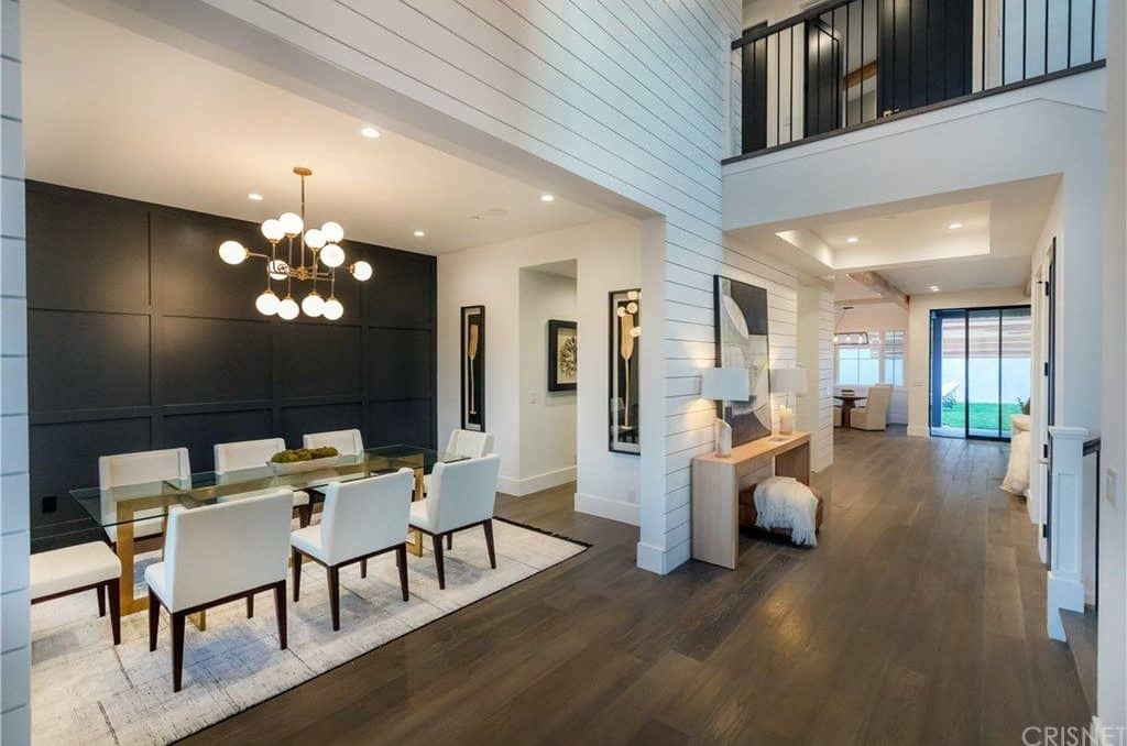 A dining area featuring hardwood floors and a white ceiling. There's a glass top dining table with white chairs, lighted by a gorgeous ceiling light.