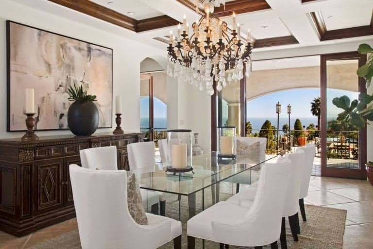 Dining room boasting a glass top dining table paired with white chairs lighted by a glamorous chandelier hanging from the stunning coffered ceiling.