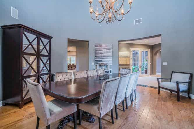 Dining room featuring a long dining table set with gray chairs lighted by a glamorous chandelier and is surrounded by blueish gray.