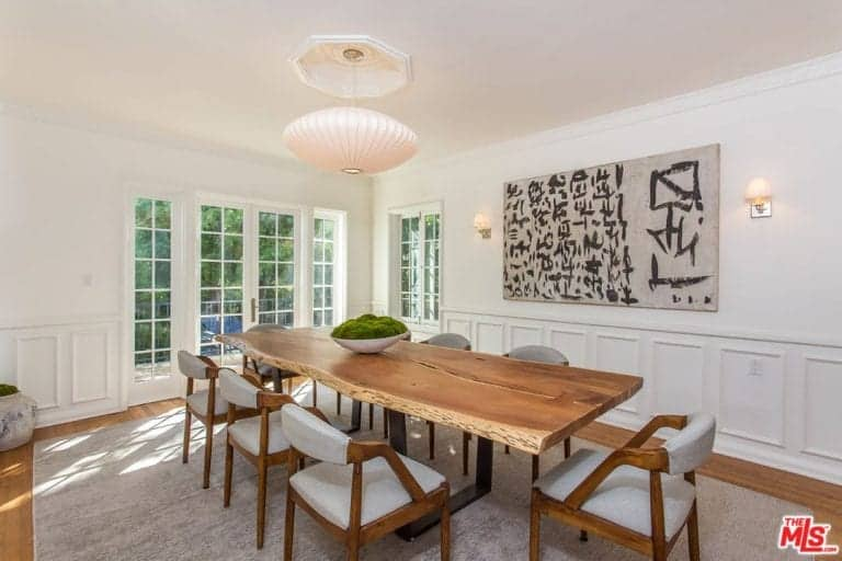 A spacious dining room boasting a rustic dining table set on top of a large area rug covering the hardwood flooring. The area has a charming ceiling light.