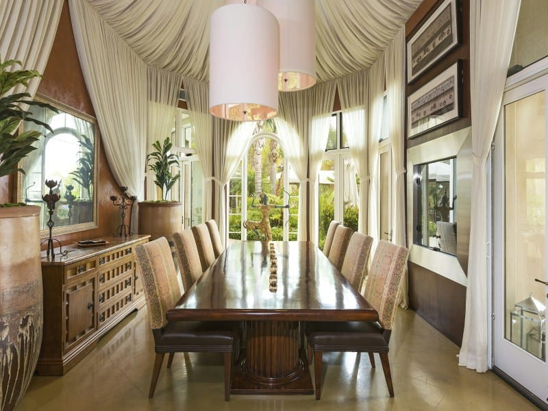 This dining room boasts a luxurious dining table and chairs set lighted by large pendant lights and is surrounded by elegant curtains wrapped around the room's walls and ceiling.