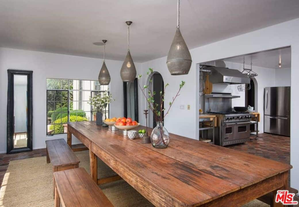 A focused look at this dining room's large rustic dining table and chairs set lighted by stylish gray pendant lights.