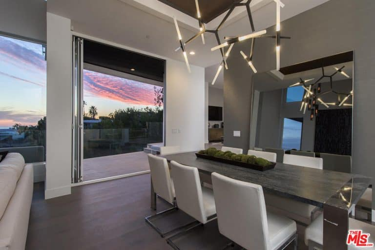 Contemporary dining room featuring a modern dining table and chairs set lighted by stunning ceiling lighting hanging from the tall tray ceiling.