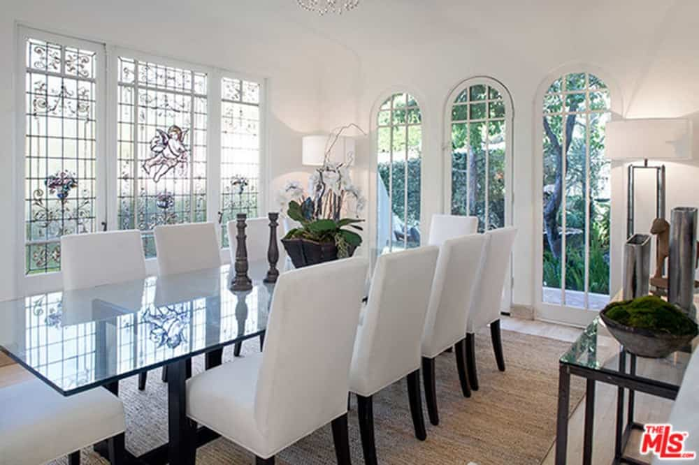 A focused shot at this dining room's glass top dining table set paired with white chairs. The room features white walls and a tall white ceiling.