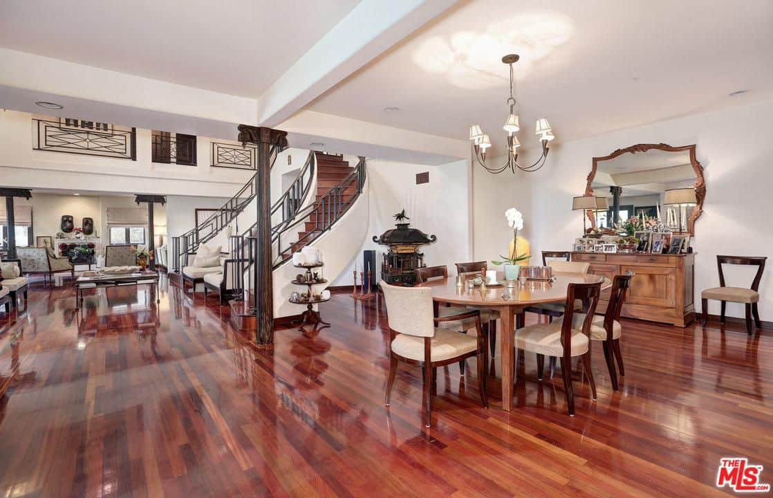 A gorgeous large house featuring reddish hardwood floors and white walls. It has a dining area featuring a classy dining table and chairs set lighted by a charming ceiling light.