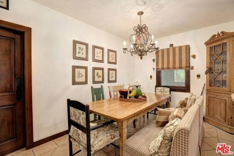 A dining room featuring a classy dining table and chairs set lighted by a charming chandelier. The room features white walls and tiles flooring.