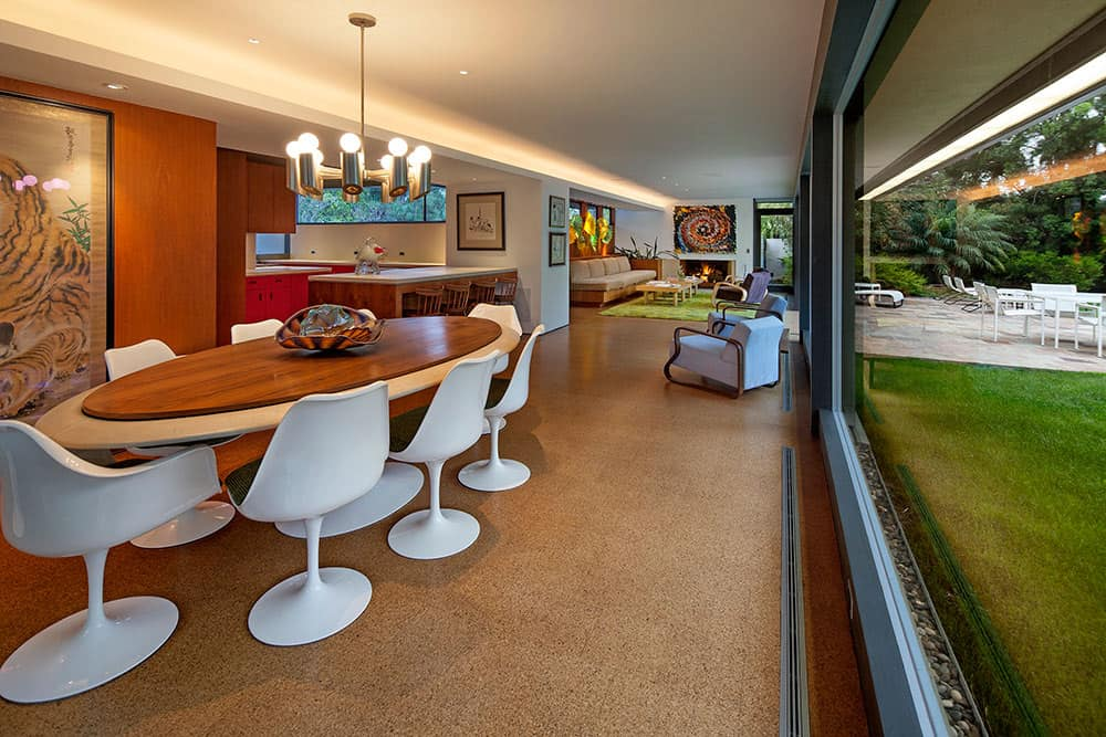 A dining area boasting a modern oval-shaped dining table with modern white chairs and is lighted by a gorgeous ceiling light.