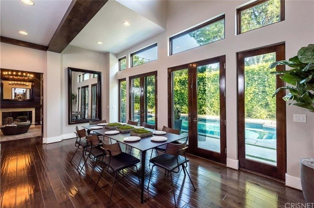 A spacious dining room featuring hardwood flooring and a tall ceiling. The area features a rectangular dining table with seats for eight.