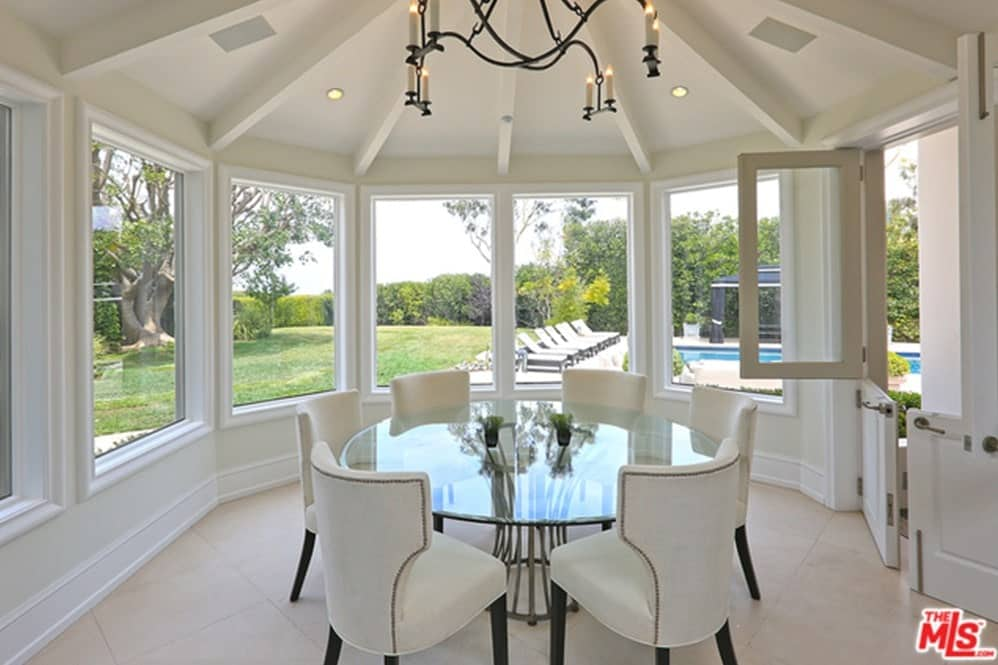 A round glass top dining table set with white chairs surrounded by glass windows and a white ceiling.