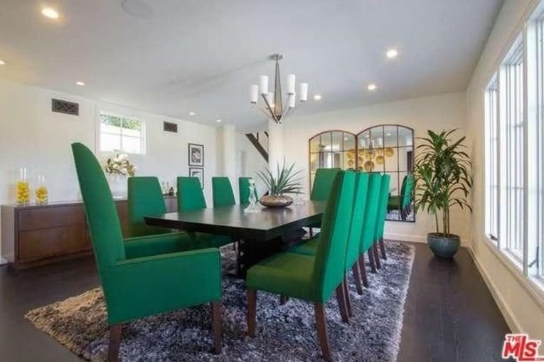 Large dining room featuring a large rectangular dining table paired with modern green chairs set on top of a large area rug covering the hardwood flooring.