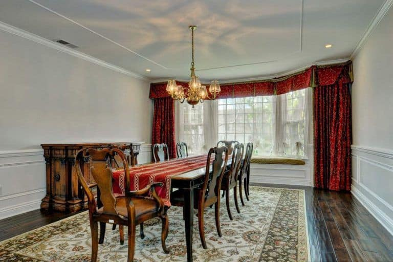 Large dining room featuring hardwood floors topped by a classy area rug where the classy dining table and chairs are set, lighted by a gorgeous ceiling light. The window boasts elegant red curtains.