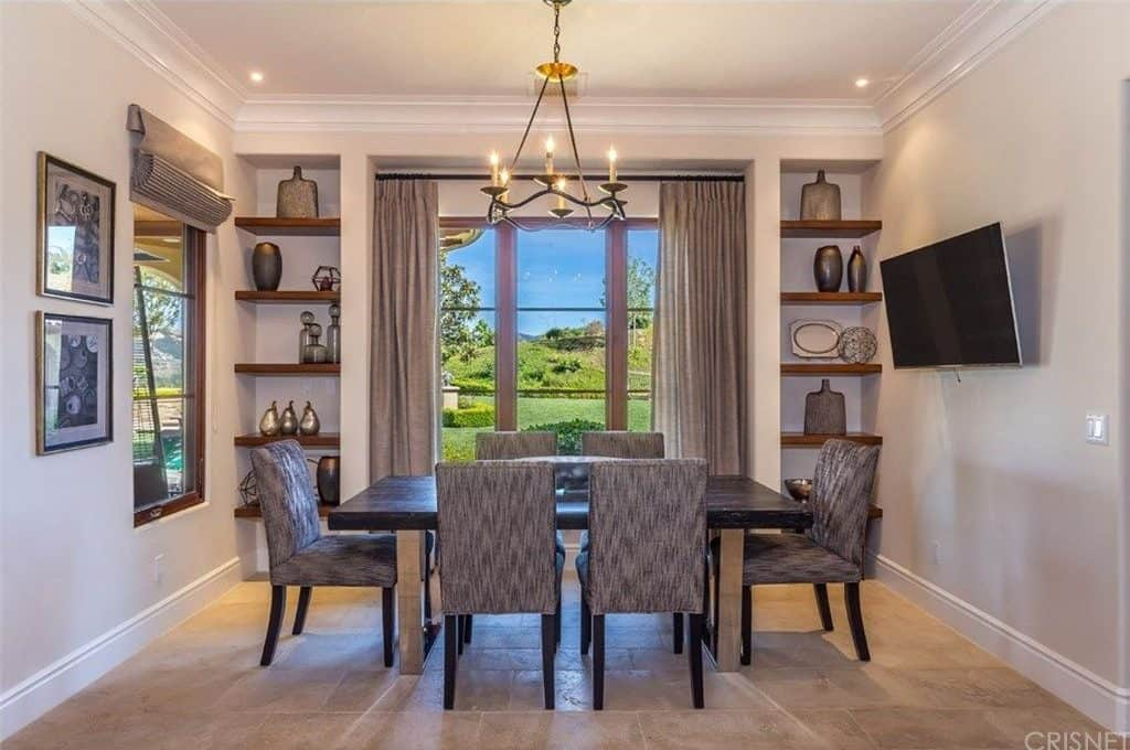 A dining room boasting a classy dining table and chairs set lighted by a lovely ceiling light. The room offers a flat-screen TV on the wall, and has built-in shelving as well.