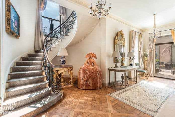 This entry hall is decorated with antique sculpture and a gilded mirror that hung above the light wood console table topped with traditional table lamps. It has a bordered rug and sleek chandelier along with a winding staircase highlighted by a gorgeous artwork.