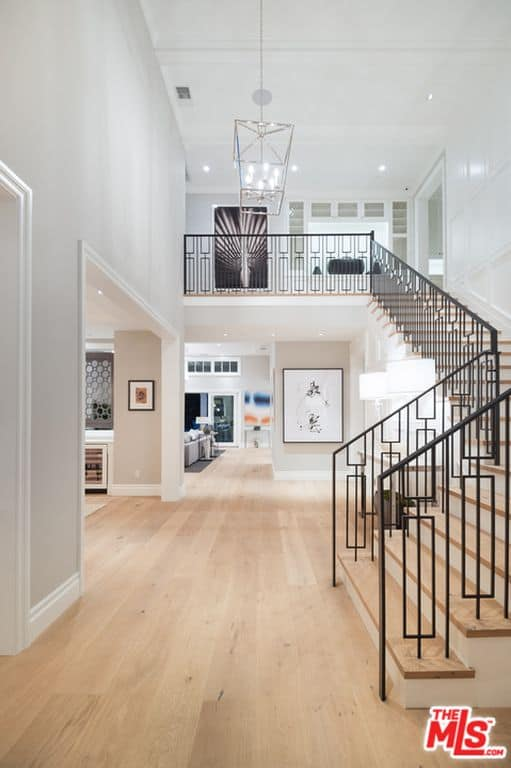 Simple foyer with light hardwood flooring and a white beamed ceiling mounted with a lantern chandelier. It includes a sleek staircase with stylish wrought iron railings that add character in the area.
