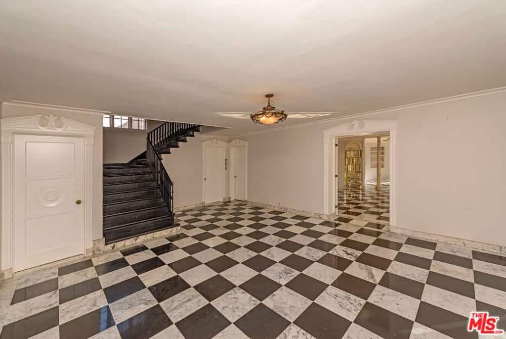 Spacious entry hall with marble checkered flooring and white walls contrasted by a black staircase. It is illuminated by a warm semi-flush mount light fixed on the regular ceiling with crown molding.