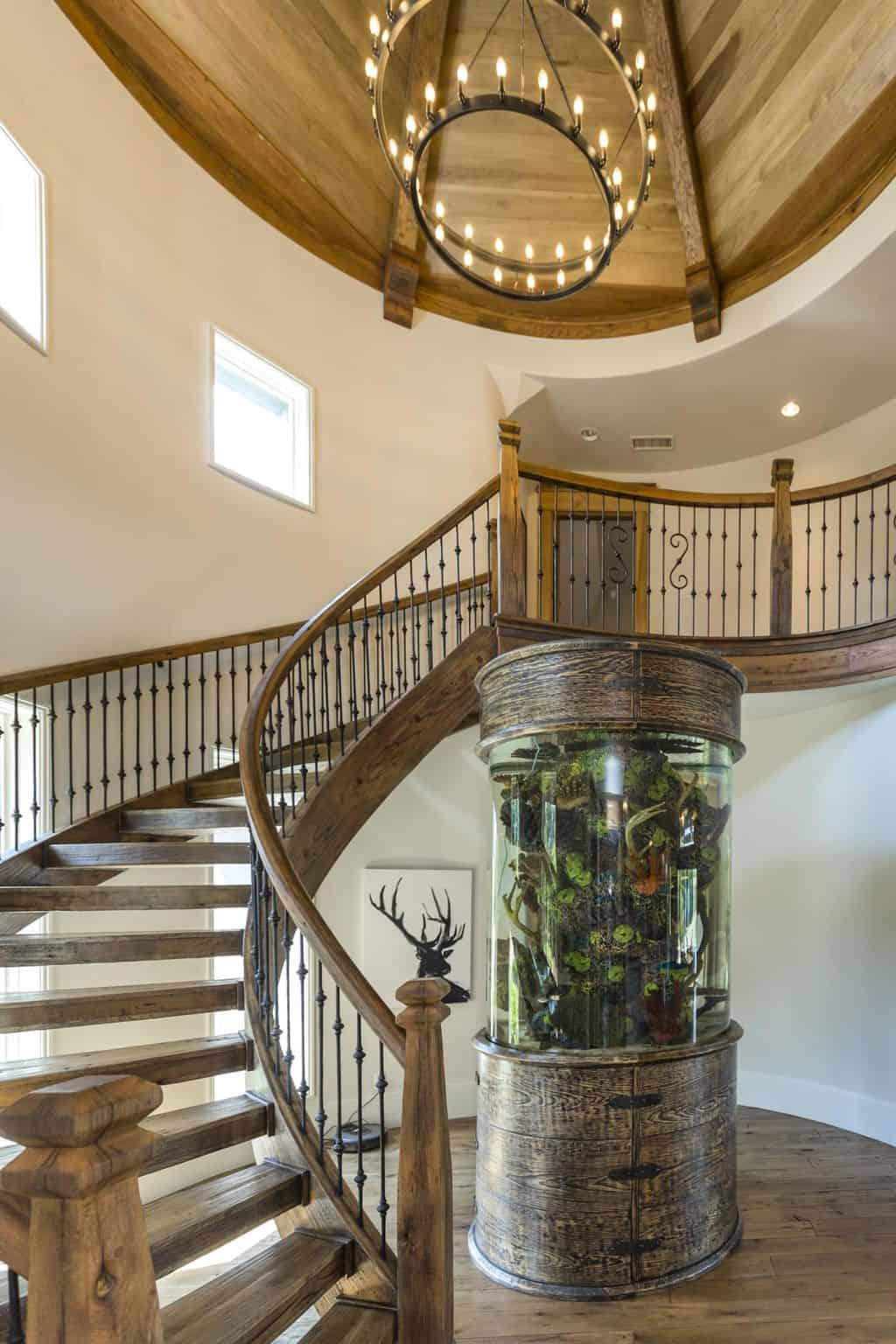 Cozy foyer decorated with a stag artwork and a spectacular fish tank situated next to the wooden staircase. It is illuminated by a two-tier chandelier that hung from the wood beam ceiling.