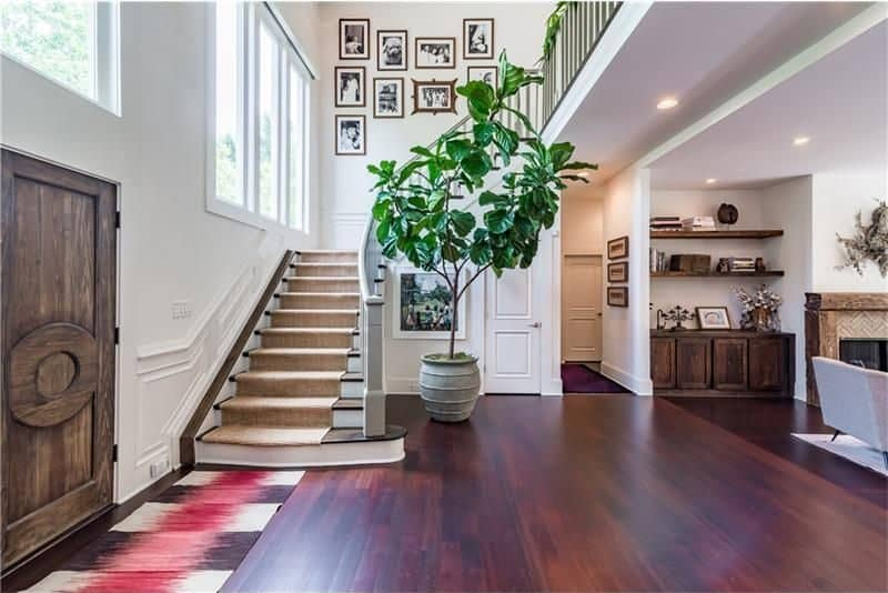 Large fiddle leaf fig plant creates a refreshing ambiance in this foyer with a natural wood entry door and a multi-colored runner that lays on the dark hardwood flooring.