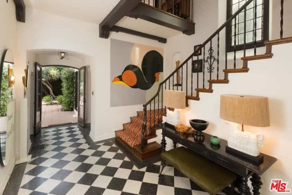 A lovely artwork brings a pop of color in this foyer with a French door and black console table that's topped with drum table lamps. It includes checkered flooring and a wooden staircase dressed in a patterned runner.